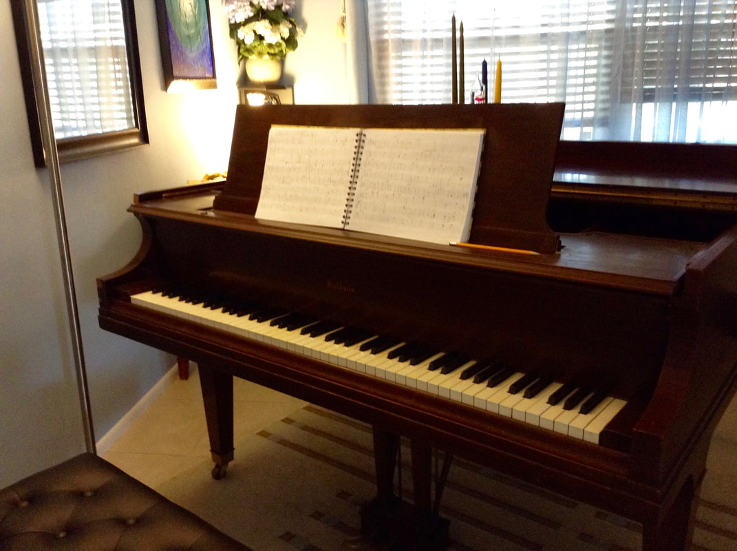 Photo of Baldwin baby grand piano with original notation and pencil on music stand and light streaming from window behind piano by Jenny Leigh Hodgins