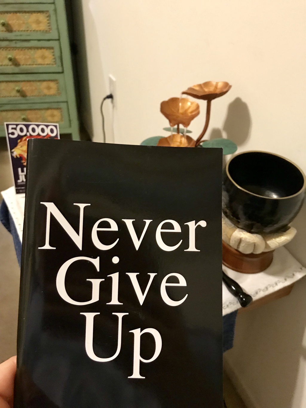 Holding a Never Give Up notebook at my Buddhist altar before my morning prayer. Photo by Jenny Leigh Hodgins